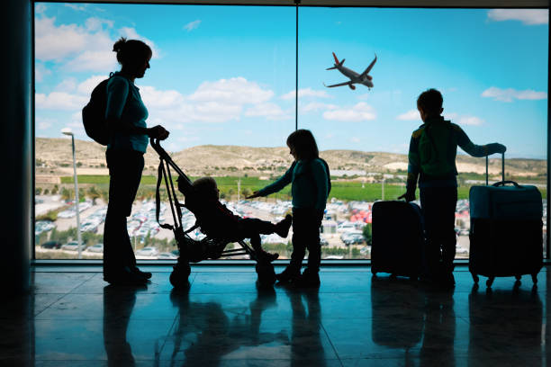 mother with kids and luggage looking at planes in airport - travel imagens e fotografias de stock