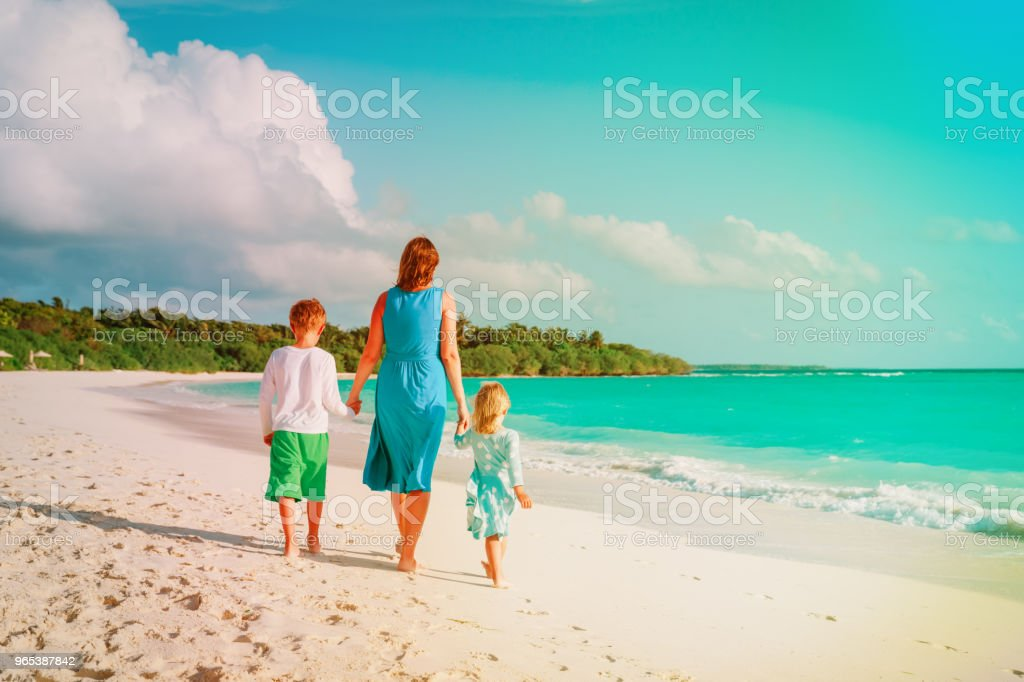 mother with kids- boy and girl- walk on beach royalty-free stock photo