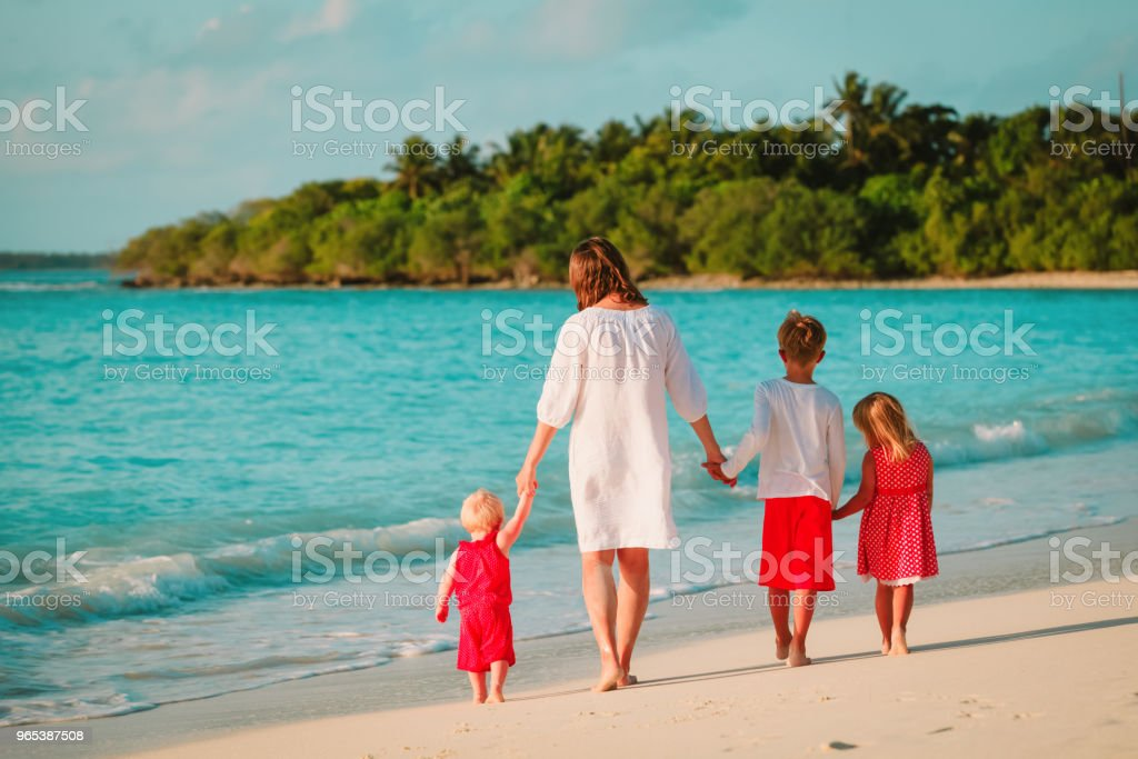 mother with kids- boy and girls- walk on beach royalty-free stock photo