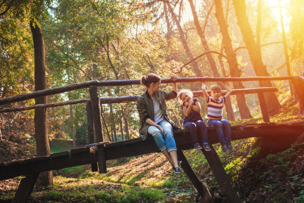 Mother with kids enjoying in sunny autumn day in nature.