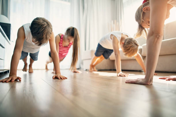 Mother with kids exercising at home stock photo
