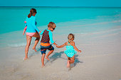 happy mother with kids play on beach, mom with son and daughters run and enjoy vacation at sea