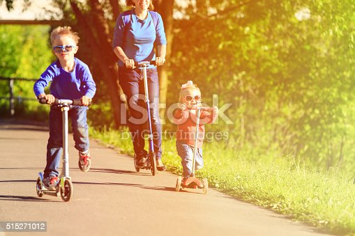 istock mother with kids riding scooters in summer 515271012