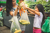 Asian mother with kids shopping in market fresh foods