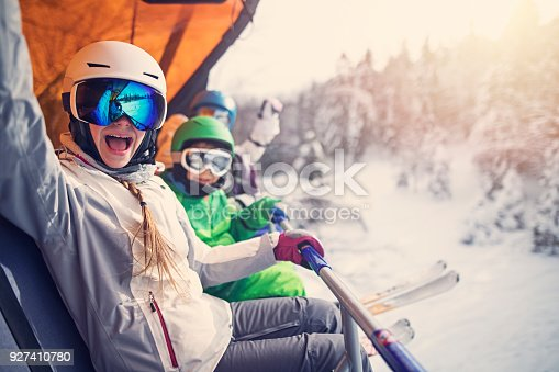 Mother skiing with kids on a sunny winter day. Family is sitting on ski slope and cheering at the camera.