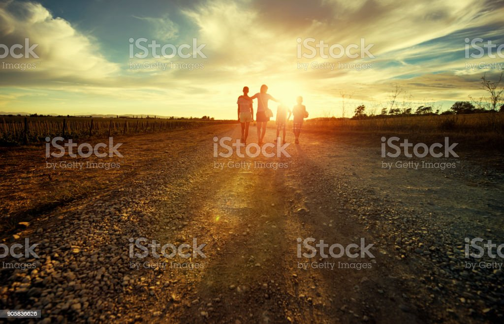 Mother with kids walking on country road stock photo