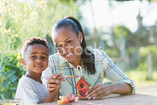 A little African American boy sitting outdoors with his mother at a table doing an arts and crafts project.  Mom is helping her son paint a tiny bird house for Earth Day.  The child is holding the paintbrush and his mother is guiding his hand.  It is a bright, sunny day and they are looking up and smiling at the camera.  The boy is 5 years old, and the woman is in hter 30s.