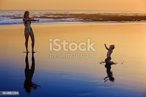 497142294 istock photo Mother with little child on the sunset sea beach 504882034