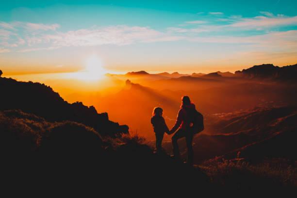 Mutter mit kleiner Tochter genießen Reisen in Sonnenuntergangsgebirge – Foto