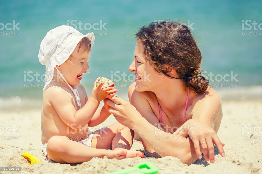 Mother with little daughter on the beach stock photo