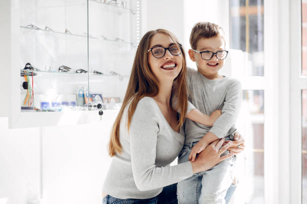 Mother with little son in the glasses store stock photo