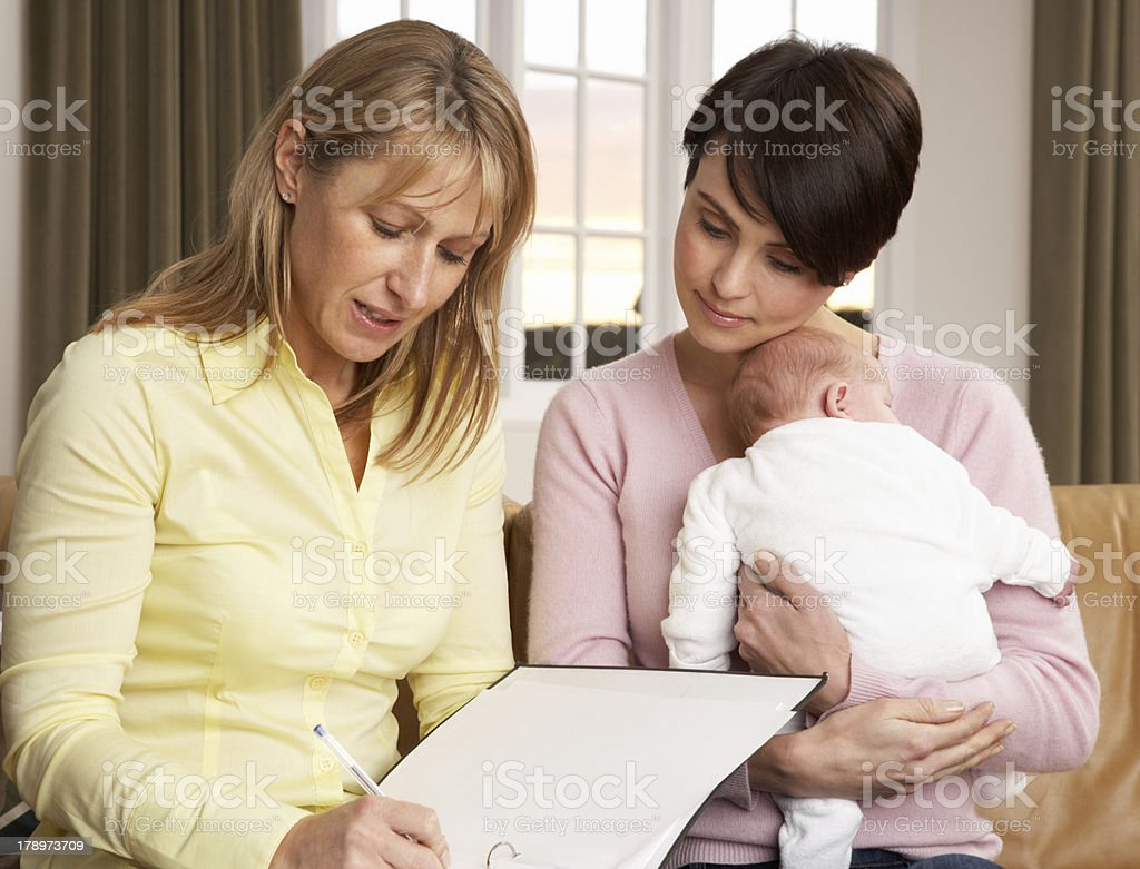 Mother With Newborn Baby Talking To Health Visitor At Home stock photo