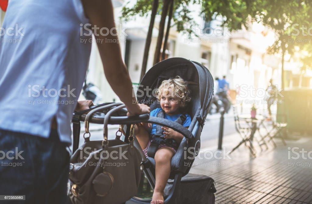 Madre con cochecito de niño en la ciudad a pie - foto de stock