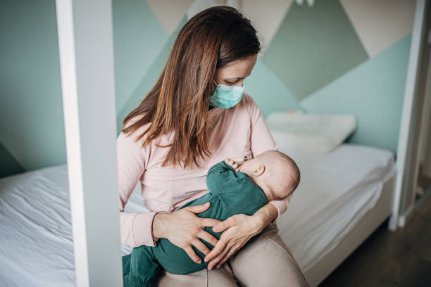 Mother with protective mask breastfeeding her baby son at home stock photo