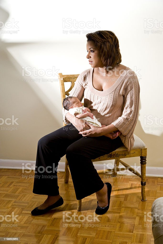 Mother with sad expression holding newborn stock photo