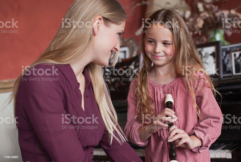 Mother with sheet music watching daughter practice on recorder royalty-free stock photo