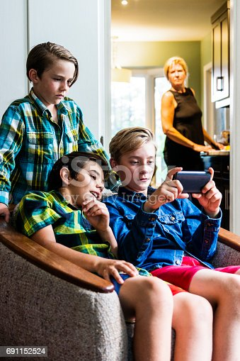 A mother looks on from the kitchen as two pre-teen boys use a smartphone in the living room.  She is out of focus but it is clear to see her sense of discomfort with what they are doing on the internet.