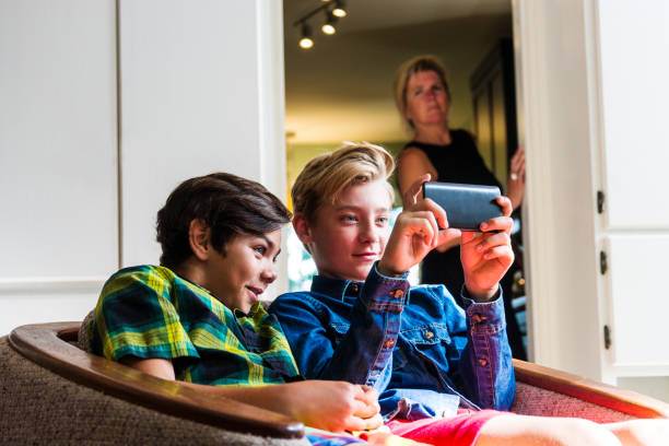 mother with slightly concerned look on her face watching boys using the internet on a phone - mom spying stock photos and pictures