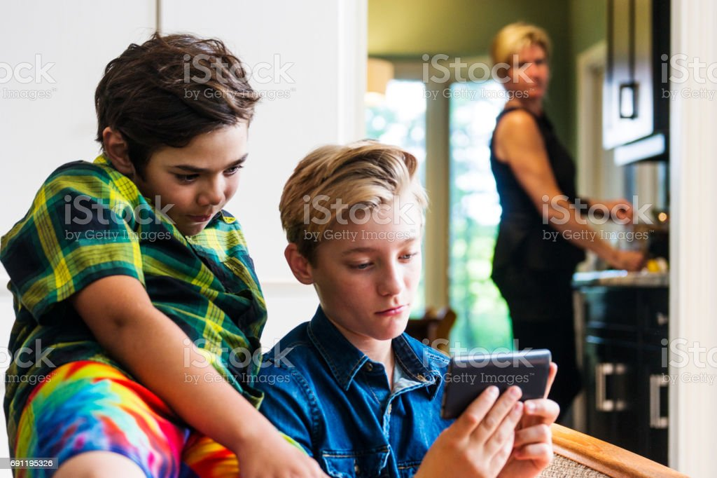 Mother with slightly concerned look on her face watching boys using the internet on a phone stock photo