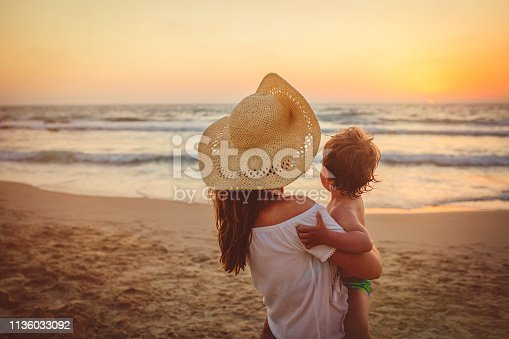 Family on holidays in sunset on the beach