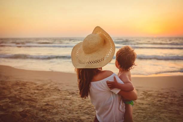 Mutter mit Sohn genießt Sonnenuntergang am Strand – Foto