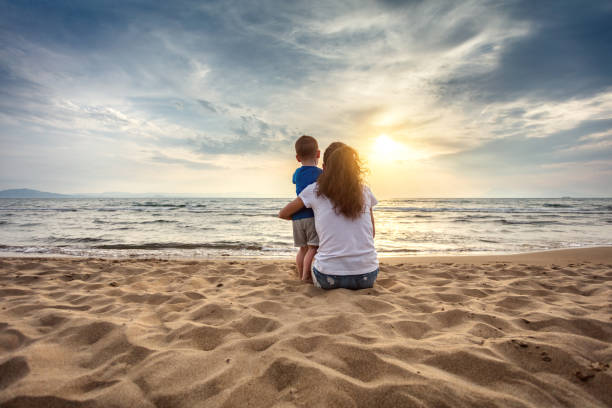 Mother with son enjoying sunset on the beach stock photo