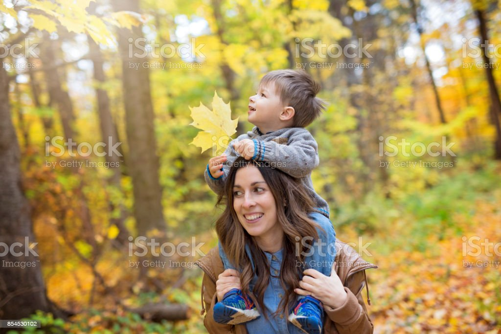 Mother with son in forest in autumn stock photo