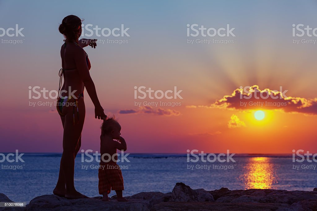 Mother with son look at sunset sun on the beach Black silhouette of happy family walking on sea beach - mother hold baby son hand, point sun and look at sunset sky. Active parent lifestyle, outdoor activity on tropical summer vacation with children Family Stock Photo