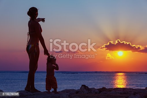 497142294 istock photo Mother with son look at sunset sun on the beach 510076098