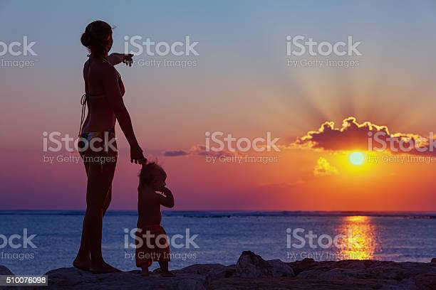 Mother With Son Look At Sunset Sun On The Beach Stock Photo - Download Image Now