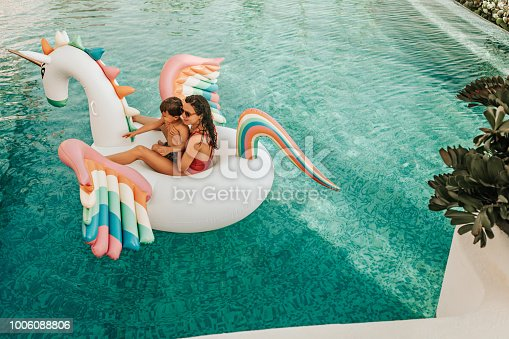 Mother with son on inflatable unicorn