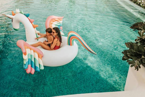 mother with son on inflatable unicorn - brinquedos na piscina imagens e fotografias de stock