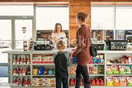 Mother with son shopping in a delicatessen store, being helped by smiling cashier.
