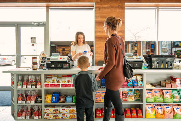 mother with son shopping in a delicatessen store - store counter stock photos and pictures