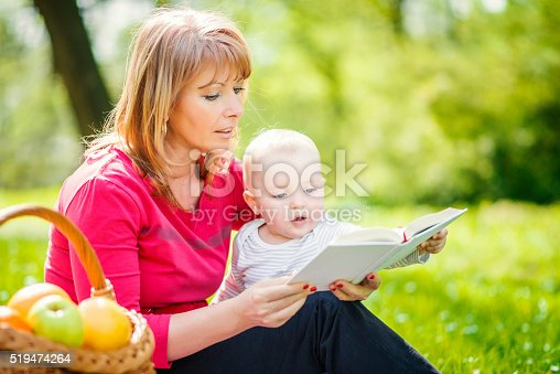 istock Mother with son sitting and read fairytale 519474264