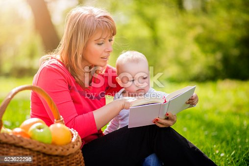 istock Mother with son sitting and read fairytale 523622298