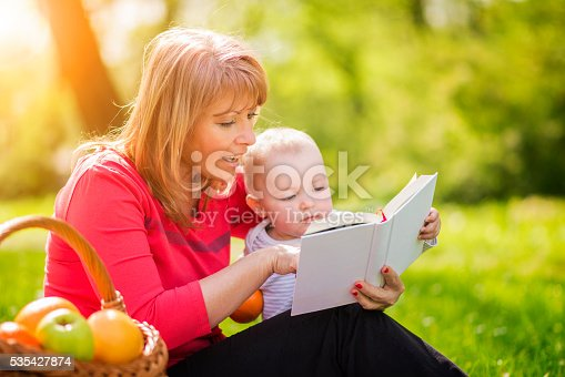 istock Mother with son sitting and read fairytale 535427874