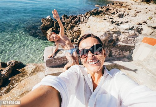 istock Mother with son take vacation selfie photo in Adriatic Sea Bay 673159436