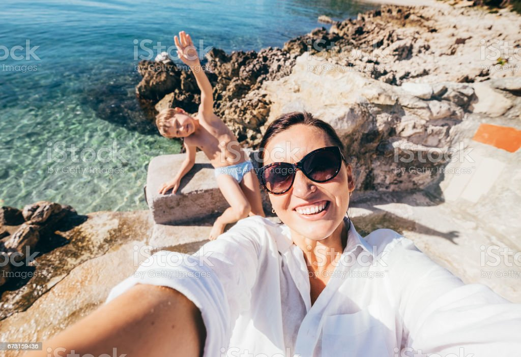 Mother with son take vacation selfie photo in Adriatic Sea Bay stock photo
