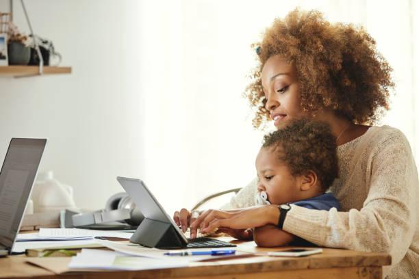 Mutter mit Sohn tippt auf digitales Tablet zu Hause – Foto