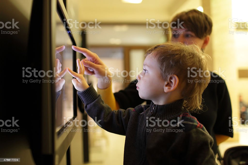 Mother with son using touch screen stock photo