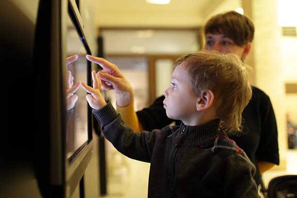 Madre con su hijo mediante pantalla táctil - foto de stock