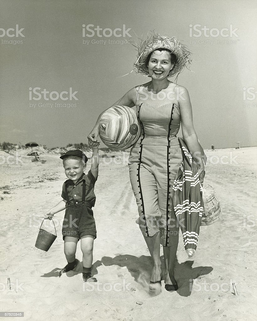 Mother with son (2-3) walking on beach, (B&W), portrait stock photo