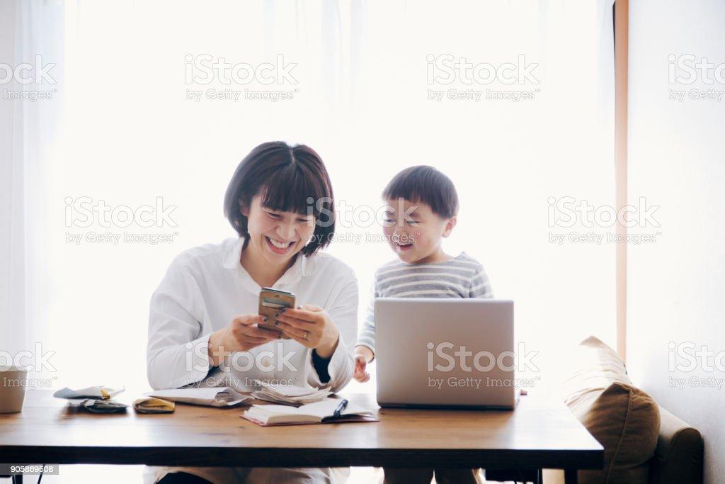 Mère avec fils travaillant à la maison - Photo