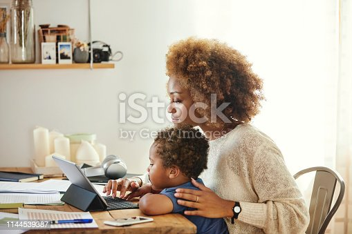 Boy looking at mother using digital tablet. Woman sitting with son at table in kitchen. She is working from home.