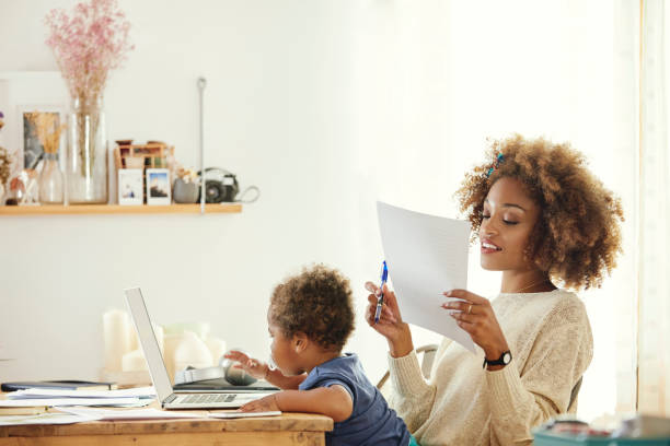 Mutter mit Sohn arbeitet auf Laptop zu Hause – Foto