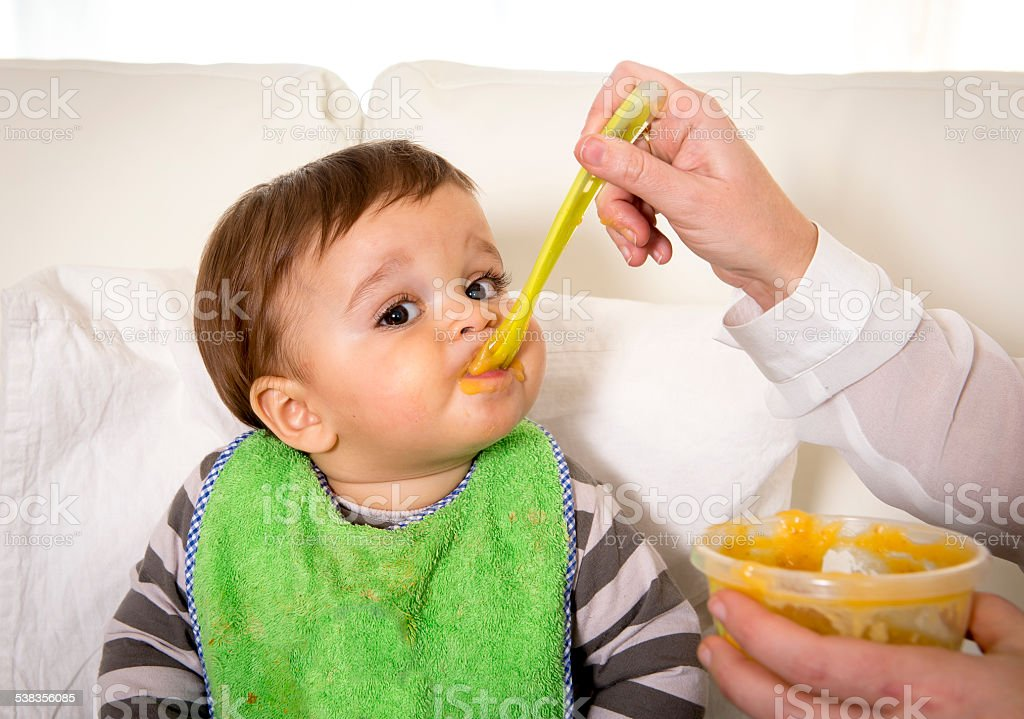 mother with spoon porridge feeding sweet baby in messy bib stock photo
