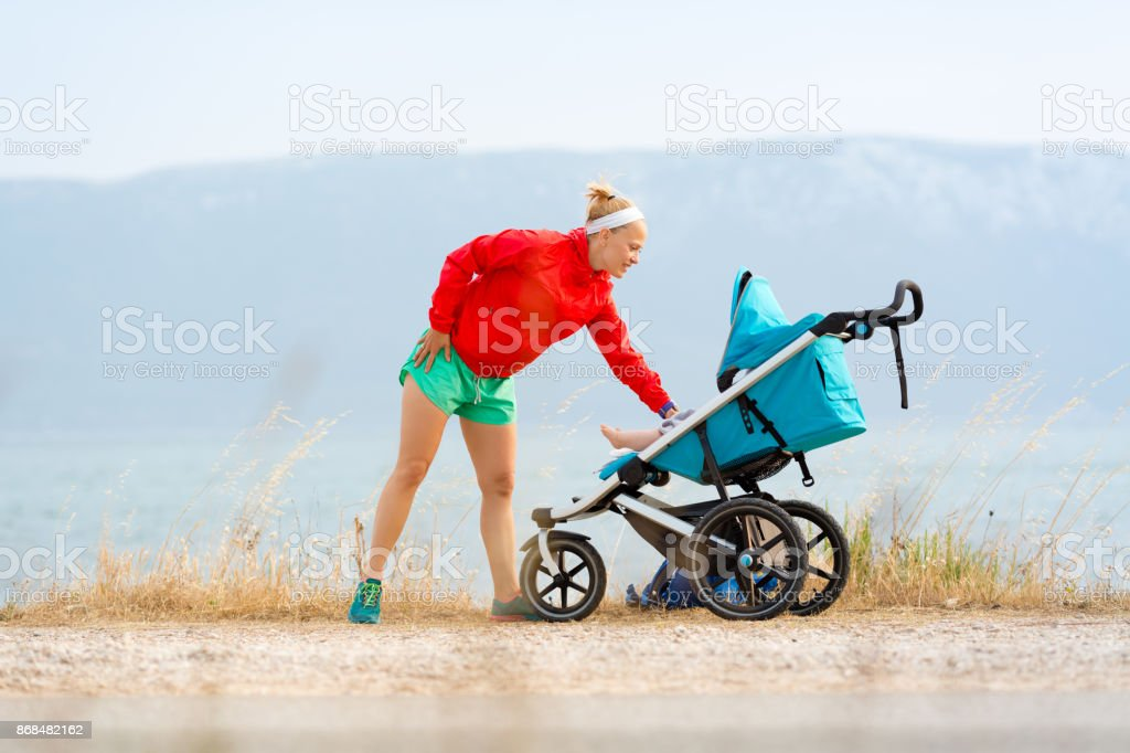 Mother with stroller enjoying motherhood at sunset landscape - Royalty-free Active Lifestyle Stock Photo