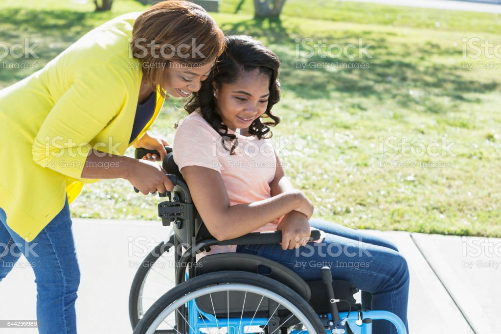 Mother with teenage daughter in wheelchair stock photo