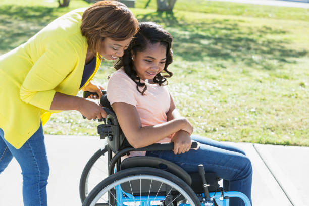 mother with teenage daughter in wheelchair - take care of your jeans imagens e fotografias de stock